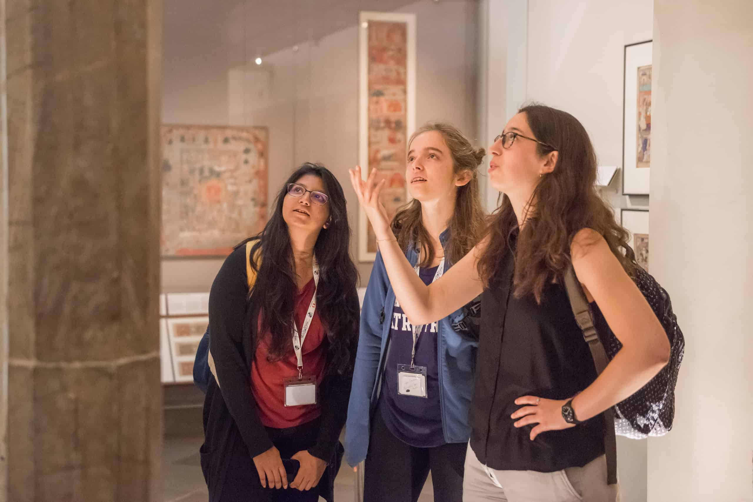 three-female-students-in-museum-looking-at-artefact