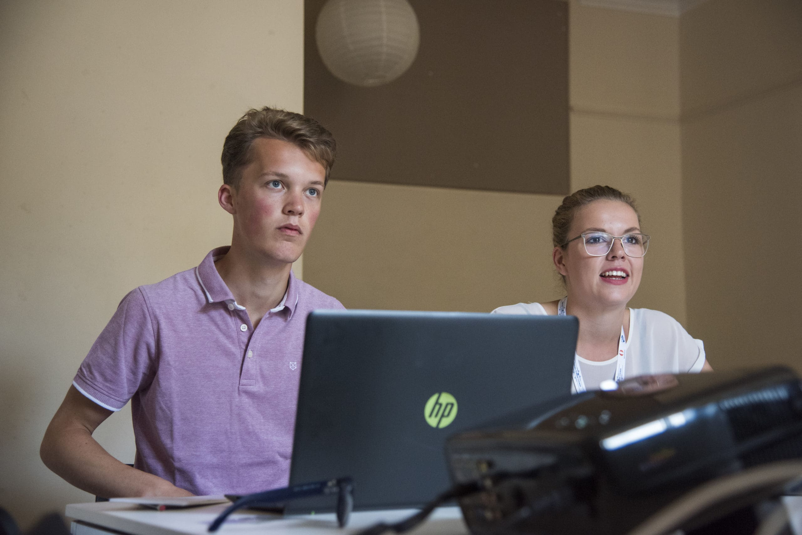 male-and-female-student-sat-behind-laptop-during-seminar