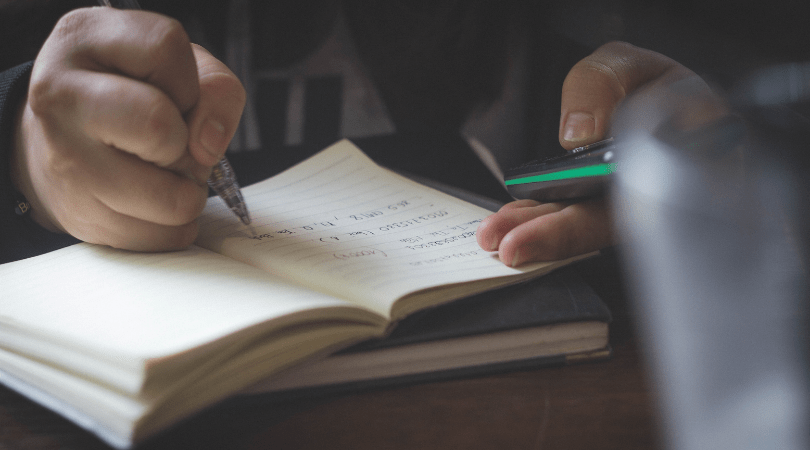 student-writing-notes-in-notebook